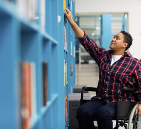 Disabled student in wheelchair choosing books while studying in college library.
