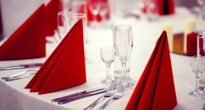 Silverware and red napkins adorn a white linen table cloth
