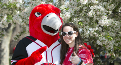 Camden Raptor mascot with Camden Alumna pointing at you!