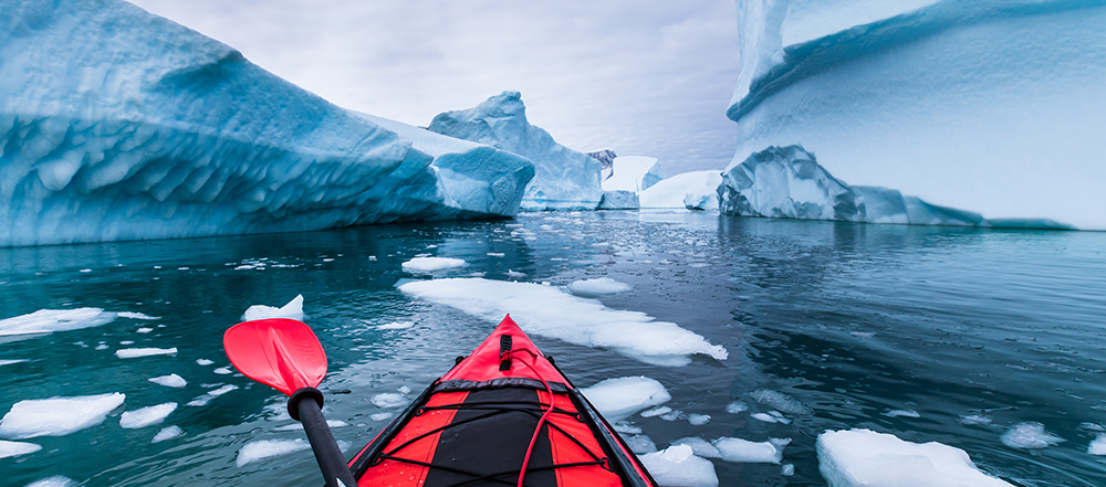 Kayaking in Antarctica between icebergs with inflatable kayak, extreme adventure in Antarctic Peninsula