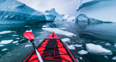 Red Kayak parting through ice covered waters