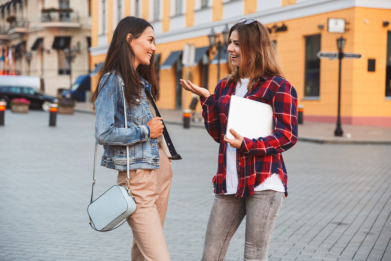 Two women talk together on city street
