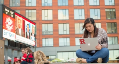 Rutgers Alumna sits outside on the New Brunswick campus with laptop