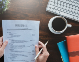 Hands holding resume with coffee and keyboard nearby
