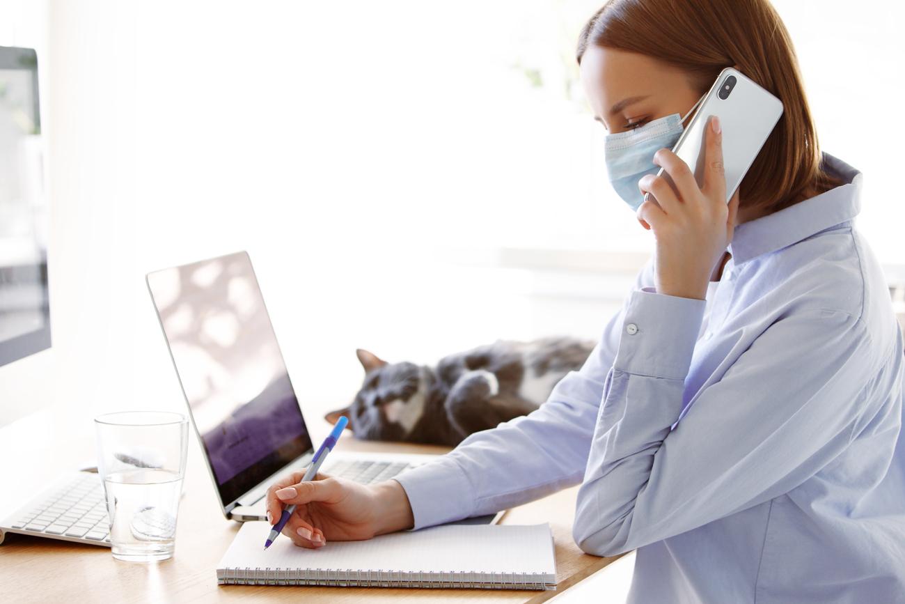 Woman taking notes at computer, wearing mask
