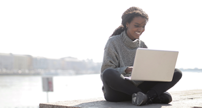 Rutgers alumna watches videos on a laptop outside