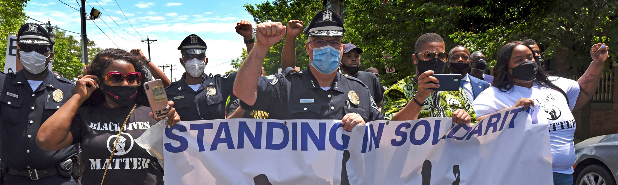 cop marching with protesters in camden