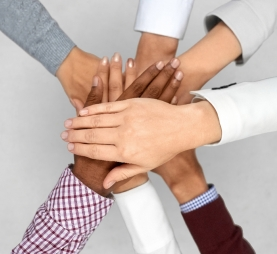 business startup and teamwork concept - diverse team putting their hands together